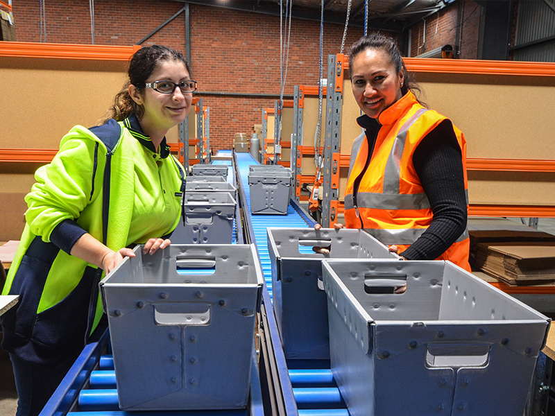 Supported worker Flory with warehouse team leader Mata at the busy conveyor
