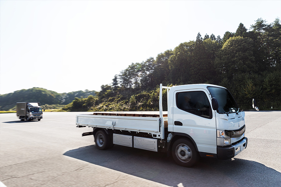 Past and present. eCanter test truck at Fuso's Kitsuregawa proving ground. In the background is a standard diesel Canter. The difference is dramatic.